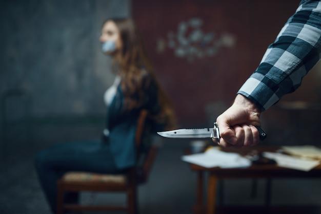 Maniac kidnapper mit einem messer, ängstliches weibliches opfer auf hintergrund. entführung ist ein schweres verbrechen, verrückter männlicher psycho, entführungshorror, gewalt