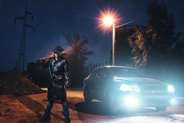 Maniac mit blutigem baseballschläger gegen schwarzes auto