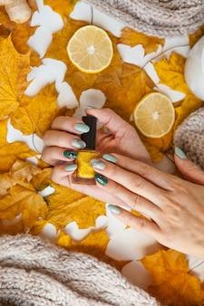 Maniküre auf grünen und grauen nägeln mit schwarzen und goldenen strasssteinen mit brillantem ornament auf handgold...