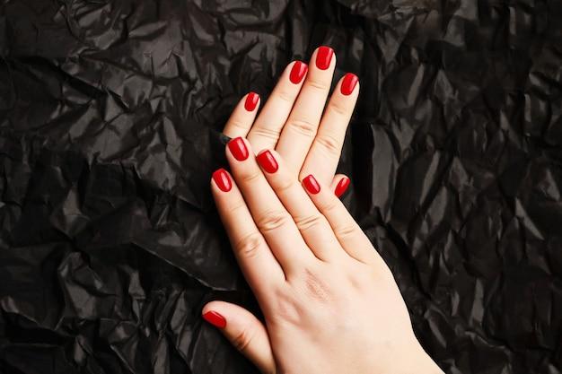 Maniküre der roten frau auf dem schwarzen hintergrund der kunstverführerische farbeglänzende nageloberfläche