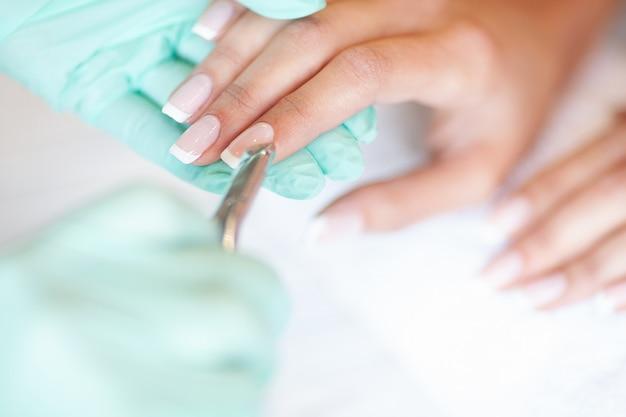Maniküre. geschickter meister der maniküre, der datei in ihren händen beim arbeiten in ihrem schönheitssalon hält