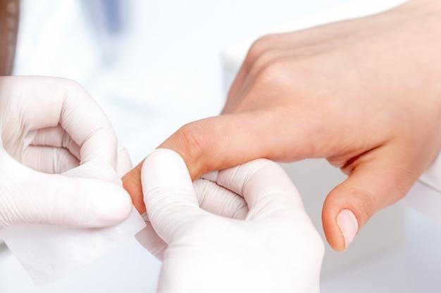Maniküre-meister, der nagellack mit weißem wattepad im schönheitssalon entfernt