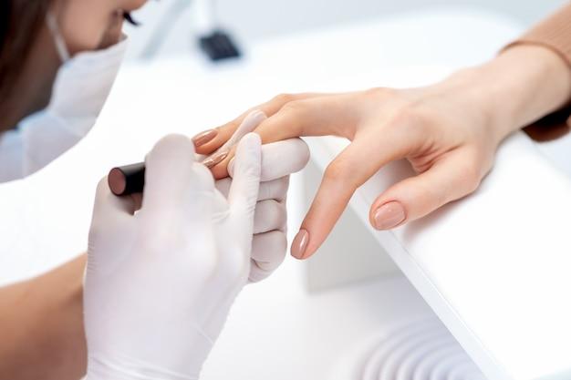 Maniküre-meister in schutzhandschuhen, die beigen nagellack auf weiblichen nägeln im schönheitssalon auftragen