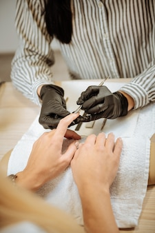 Maniküre-meister. maniküre-meisterin fühlt sich äußerst verantwortungsbewusst und beschäftigt, während sie maniküre für ihren kunden macht