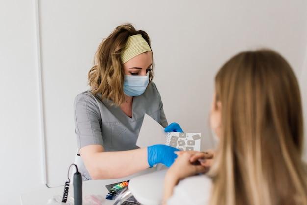 Maniküre-meisterin in einem schönheitssalon arbeitet mit den händen des kunden