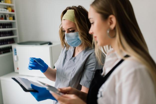 Maniküre mit schutzmaske, die weibliche nägel mit nagellack in einem maniküresalon malt.