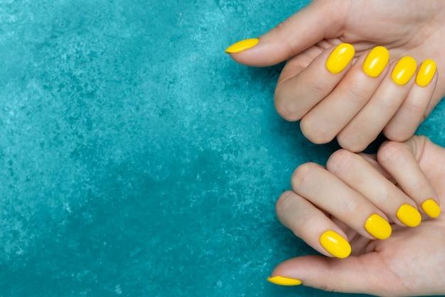 Maniküre mit trendiger gelber farbe des nagellacks auf weiblichen händen. minimales design.