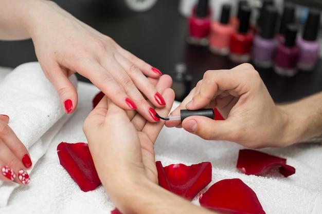 Maniküre. nahaufnahme der schönen frau hände poliert nägel mit rotem nagellack im schönheitssalon. nahaufnahme von kosmetikerin, die weibliche kundennägel malt. schönheitskonzept. hohe auflösung