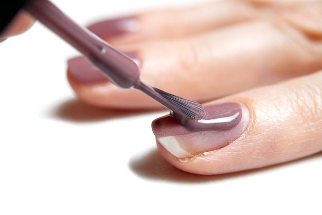 Maniküre. nahaufnahmeaufnahme einer frau, die nägel der hand poliert - maniküre. junge kaukasische frau, die eine französische maniküre erhält. nageltechniker maniküre im nagelstudio