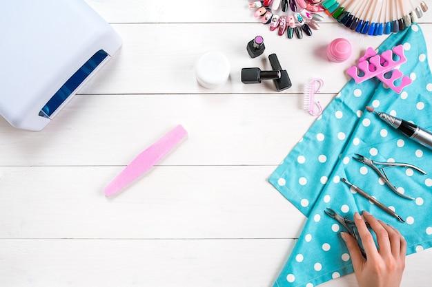 Maniküre-set und nagellack auf holzuntergrund. ansicht von oben. platz kopieren. stillleben. nagelpflege.