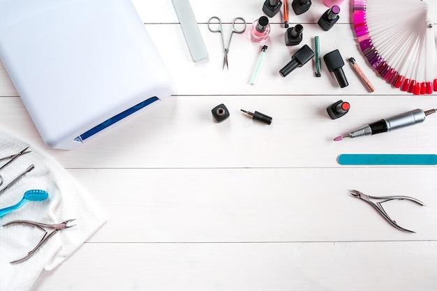 Maniküre-set und nagellack auf holzuntergrund. nahaufnahme. ansicht von oben. platz kopieren