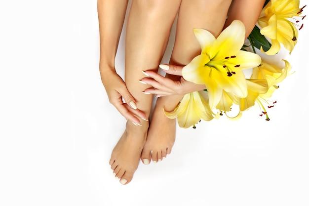 Maniküre und pediküre an langen ovalen nägeln mit gelben lilien auf weißem grund.