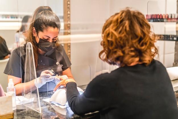 Maniküre- und pediküre-salon, coronavirus, covid-19, soziale distanz. die wiedereröffnung aufgrund der pandemie, sicherheitsmaßnahmen. ein arbeiter und ein klient mit masken