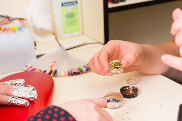 Maniküre zeigt weiblichen kunden einen kleinen topf mit goldenem nagelglitter mit fingernägeln in folienverpackungen - auswahl der farbe für die gel-maniküre