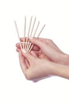 Manikürist beim reinigen der nagelhaut an den weiblichen fingern mit kosmetikstift