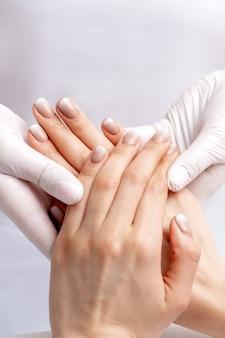Manikürist, der handschuhe trägt, die wachsmassage auf weiblichen händen mit maniküre im nagelstudio tun