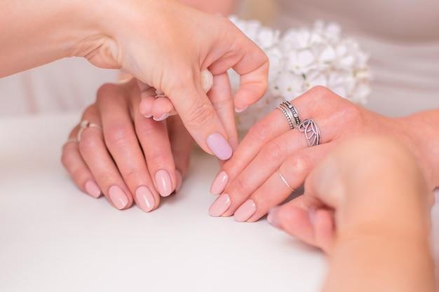 Manikürist, der weibliche hände mit romantischen manikürennägeln, nacktem gelpolitur und weißen blumen hält