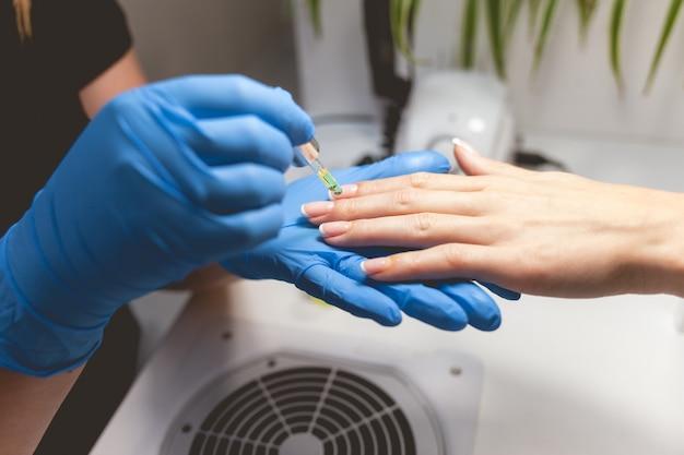 Manikürist nährt nagel- und nagelhautöl