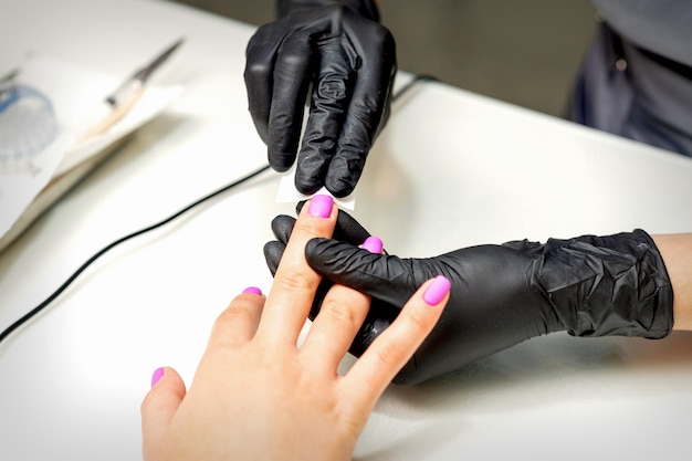 Manikürist trägt eine matte beschichtung mit einer serviette auf weibliche rosa nägel in einem nagelstudio auf