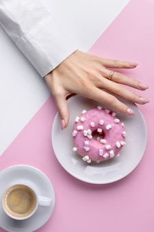 Manikürte frauenhand mit weißer tasse kaffee und donut
