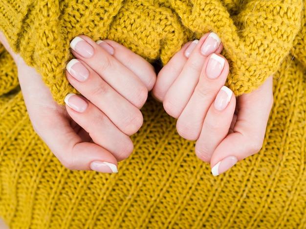 Manikürte hände, die gemütliche gelbe strickjacke halten