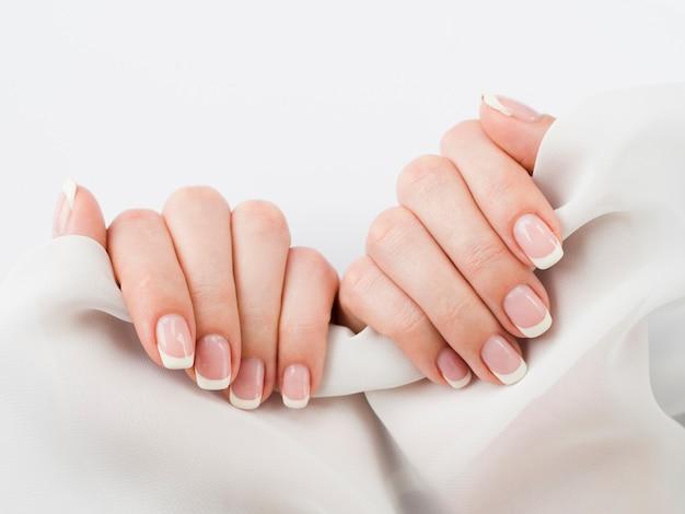 Manikürte hände, die weiches gewebe halten