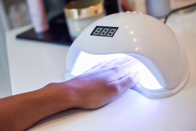 Manikürte nägel in der uv-lampe im schönheitssalon.