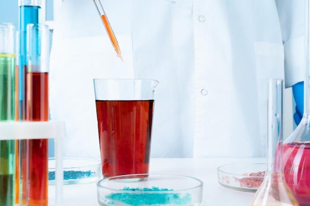Manipulationen mit chemischen glasbehältern des labors auf tabelle