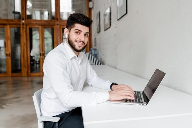Mann am arbeitsplatz mit laptop im büro