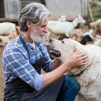 Mann am bauernhof, der mit hund spielt