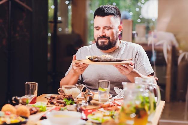 Mann am großen tisch mit essen.