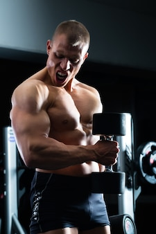 Mann am kurzhanteltraining im fitnessstudio