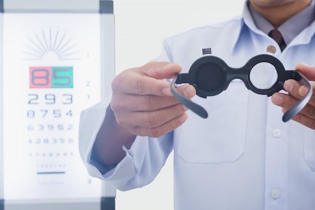 Mann am optiker, der augen hält, überprüfte werkzeug, um patienten an zu setzen