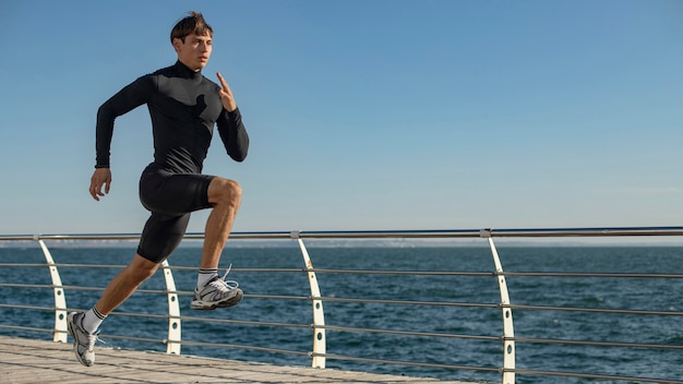 Mann am strand, der in aktivkleidung joggt