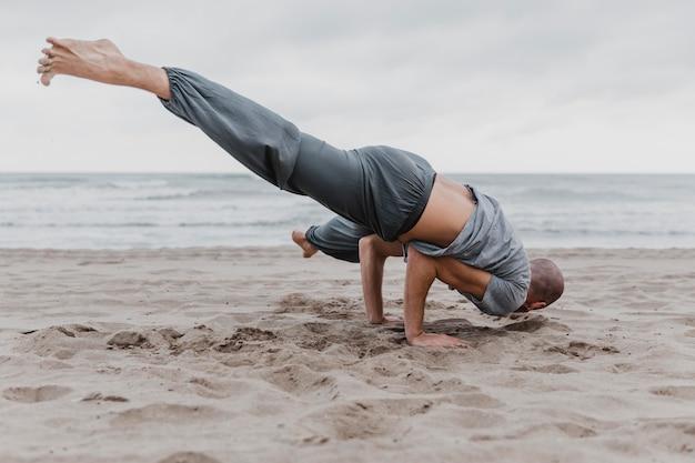 Mann am strand, der schwierige yoga-stellungen praktiziert