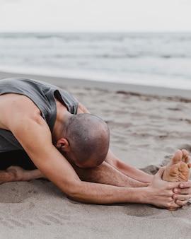 Mann am strand, der yoga-positionen auf sand ausübt