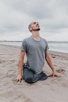 Mann am strand, der yoga-positionen ausübt