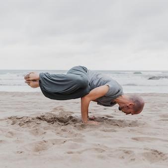 Mann am strand, der yoga praktiziert