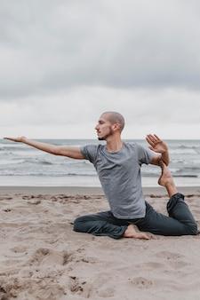 Mann am strand, der yogaübungen praktiziert