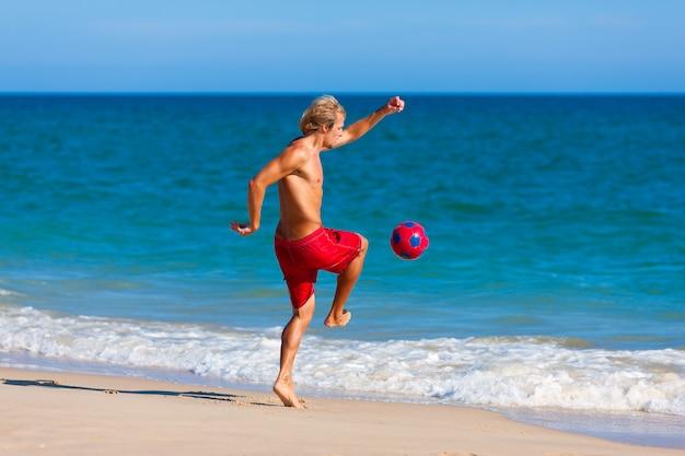 Mann am strand fußball spielen