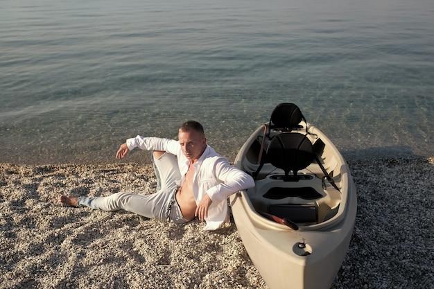 Mann am strand nahe kanuboot auf sonnigem sommertag meeresoberfläche in