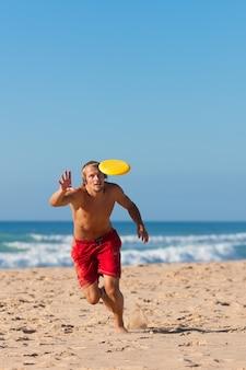 Mann am strand spielt frisbee