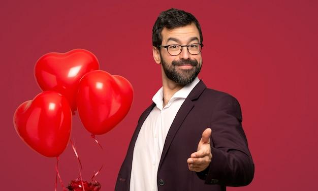Mann am valentinstag, der hände für das schließen ein gutes abkommen über rotem hintergrund rüttelt