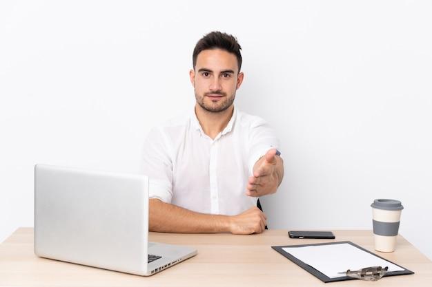 Mann an einem arbeitsplatz mit einem laptop