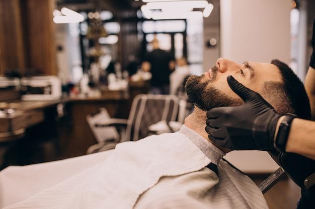 Mann an einem friseursalon, der haarschnitt und bartschnitt tut