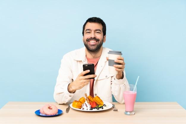 Mann an einem tisch, der frühstückswaffeln und einen milchshake hält kaffee zum mitnehmen und ein mobile hat