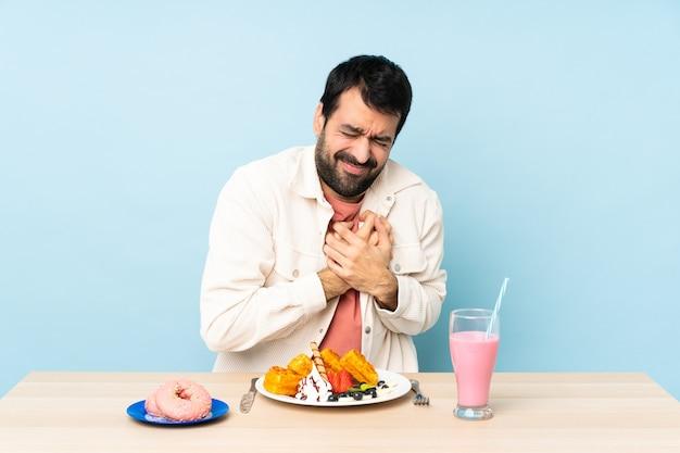 Mann an einem tisch, der frühstückswaffeln und einen milchshake hat, der einen schmerz im herzen hat
