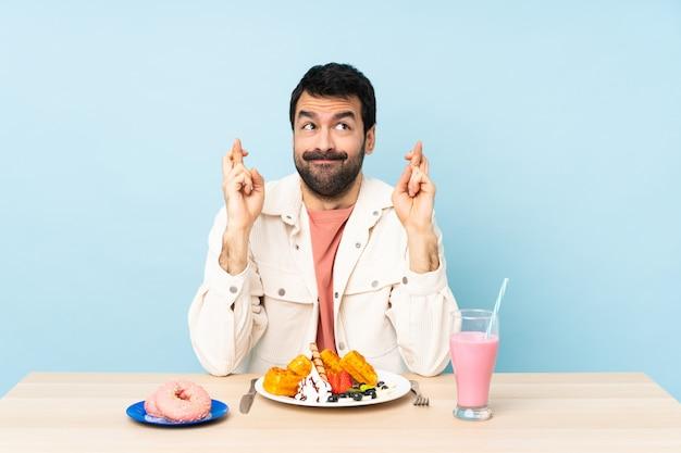 Mann an einem tisch, der frühstückswaffeln und einen milchshake mit gekreuzten fingern hat und das beste wünscht