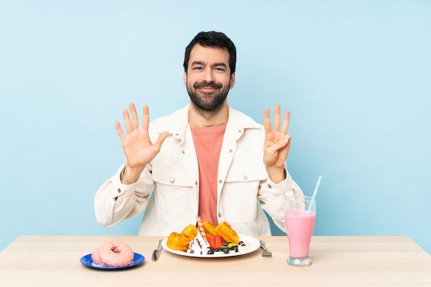Mann an einem tisch, der frühstückswaffeln und einen milchshake zählt acht mit den fingern hat