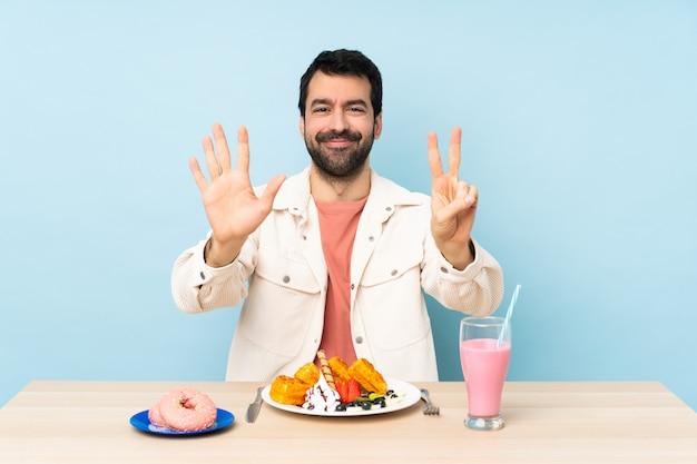 Mann an einem tisch, der frühstückswaffeln und einen milchshake zählt sieben mit den fingern hat